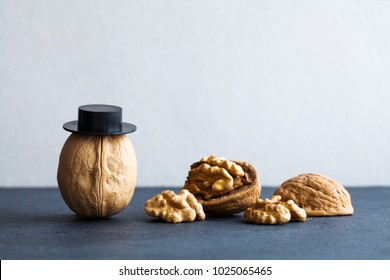 Senor walnuts black hats, half nutshell on stone and gray background. Creative food design poster. Macro view selective focus photo.