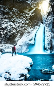 Sense of adventure at a cold frozen Wahclella Falls in an Oregon winter  with a man in a red jacket