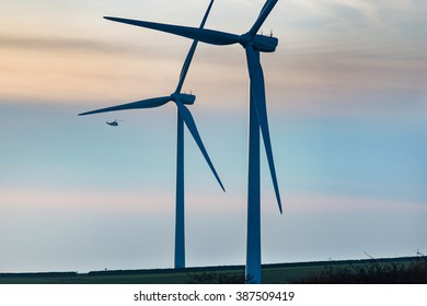 A sense of scale when a helicopter flies past a windfarm at sunset. Fullabrook, North Devon. January