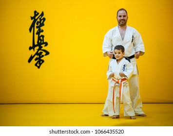 Sensei with his disciple posing in a dojo.  With the word kyokushinkai on the background. Which means: the last truth associated.