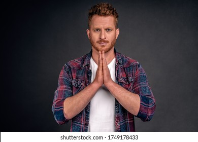 Sensei, I am listening.Portrait of serious-looking handsome adult redhead with muscles, holding hands in pray, making namaste gesture or bowing in asian style, staring strict at camera over grey wall.
