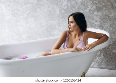 Sensetive portrait of an expecting woman. Beautiful pregnant woman in pink lingerie lies in a bath full of pink flowers and milk
