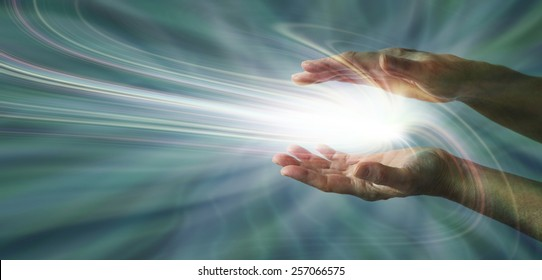 Sensing Supernatural Energy - Parallel female hands with a swirling light burst between on a blue energy field background