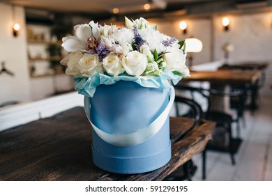 Sensitive image of amazing bouquet of white roses, flowers in blue pail on table in vintage apartment. Present, event, holiday, gratulations, gift