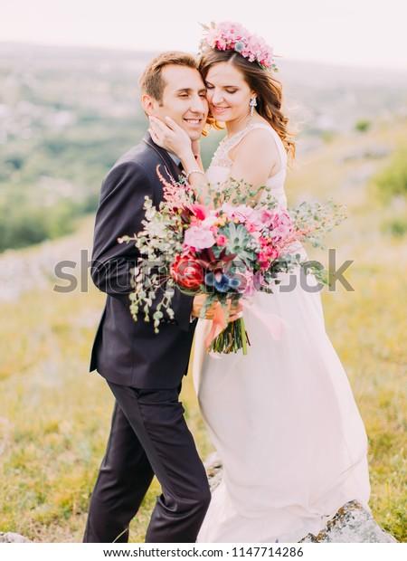 Sensitive portrait of the smiling hugging newlyweds holding the huge wedding bouquet.