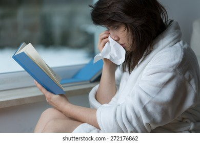 Sensitive young woman reading romance and crying