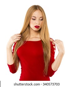 sensitive young woman straightens her hair. red dress and lipstick
