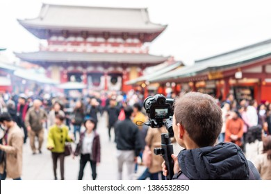 Sensoji temple in Tokyo, Japan Asakusa with red architecture and crowd of people by incense smoke and man photographer videographer filming with camera and gimbal