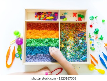 Sensory box with rainbow rice inside. Children's hands touch the texture and pour. Tool for sorting tongs and spoon. Montessori material baby