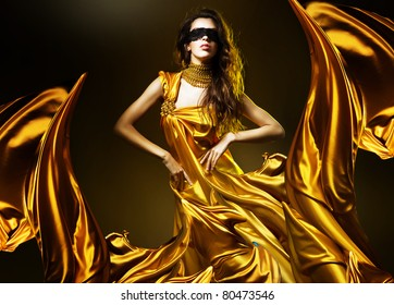 sensual adult woman in golden fabric and mask