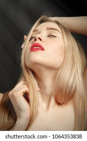sensual aroused blond woman with closed eyes on black background with light rays