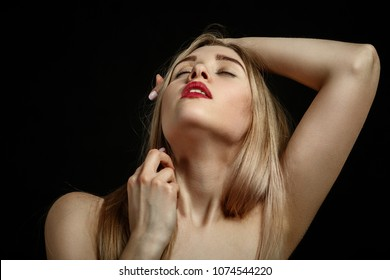 sensual aroused blond woman with closed eyes on black background