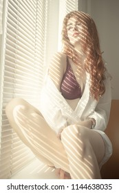 sensual aroused girl in lingerie sitting on window in sunlight with blinds