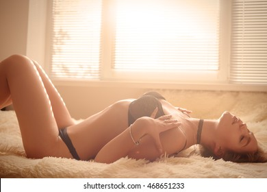 sensual aroused girl lying in sunlight, toned image