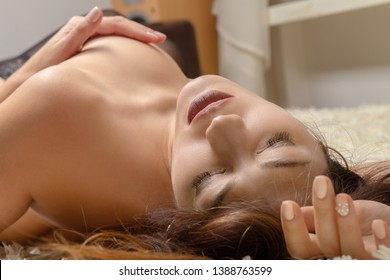 sensual aroused nude woman lying on bed, cover her breasts, have orgasms