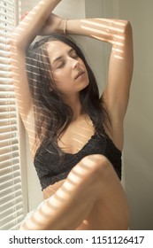 sensual aroused woman at window with blinds ans sunlight