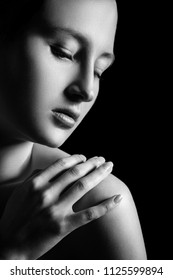 sensual aroused young woman with closed eyes on black background, monochrome
