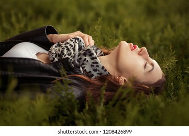 sensual aroused young woman in leather coat lying on green grass
