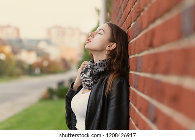 sensual aroused young woman in leather coat standing near bricks wall