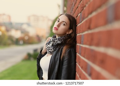 sensual aroused young woman in leather coat standing near bricks wall, looking at camera