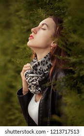 sensual aroused young woman in leather coat near green grass wall