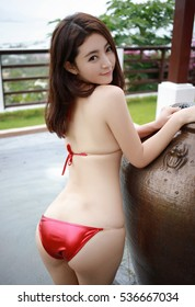 sensual asian sexy woman Japanese young lady girl wearing shiny red leather thong bikini by a swimming water pool on the rooftops garden in Southeast Asia style hotel with nice scenery in sex pose