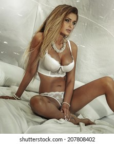 Sensual attractive blonde woman lying in white bed, wearing sexy lingerie and jewelry, posing.