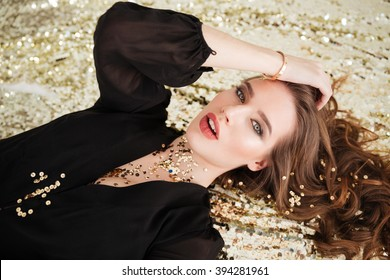 Sensual attractive young woman with sequins on her face lying over glittering background