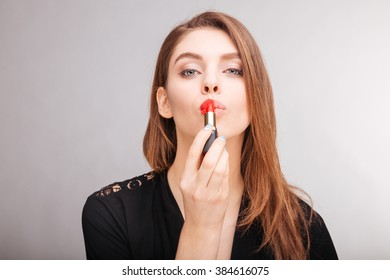 Sensual attractive young woman using and demonstrating red lipstick on her lips over white background
