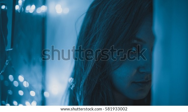 Sensual backlit portrait of a young woman on a christmas lights background