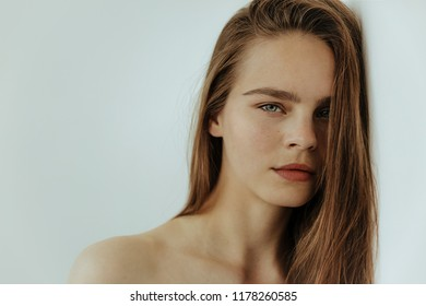 Sensual beaity Portrait of attractive young girl with bare shoulders is looking at camera, isolated on white, close up