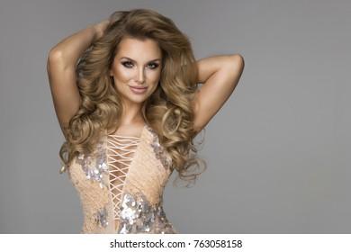 Sensual beautiful blonde woman posing in shining dress. Girl with long curly hair.