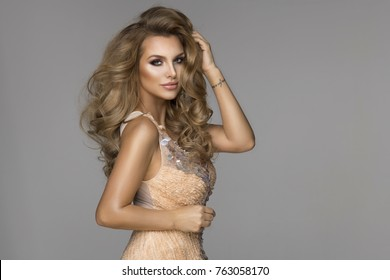 Sensual beautiful blonde woman posing in shining dress. Girl with long curly hair.