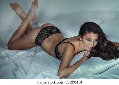 Sensual beautiful brunette woman posing in lingerie, lying in bed, smiling to the camera.