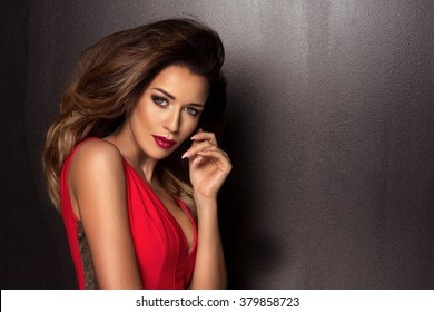 Sensual beautiful brunette woman posing in red dress. Girl with long curly hair.