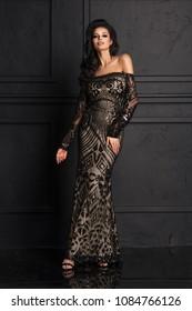 Sensual beautiful brunettee woman posing in long black dress. Girl with long curly hair.