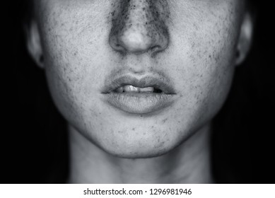Sensual beautiful freckles woman mouth close up image against black background. Black and white image.