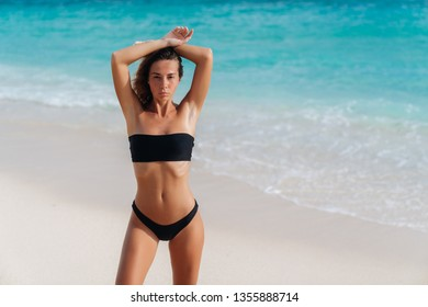 Sensual beautiful girl in black swimsuit resting near ocean on beach. Tanned young woman on vacation at resort. Concept sea, travel, swimwear