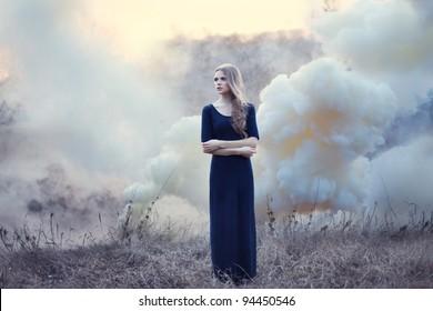 sensual beautiful girl in smoke on nature on sunset