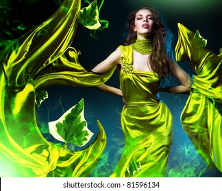 sensual beautiful woman in green fabric and leaves