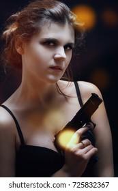 sensual beautiful woman with gun on black background
