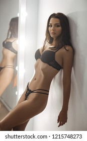 Sensual beautiful woman with long hair and perfect slim body posing at home near mirror wearing sexy lingerie. Elegant female model in sexy lingerie standing on white gray wall and sensually poses
