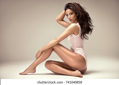 Sensual beautiful woman with long hair and perfect slim body posing in studio.