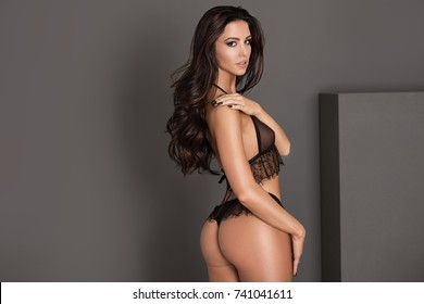 Sensual beautiful woman with long hair and perfect slim body posing in studio wearing black sexy lingerie.