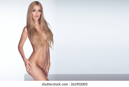 Sensual beautiful woman with perfect slim body posing naked, looking at camera. Studio shot.