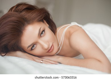 Sensual and beautiful woman in white dress in the bed