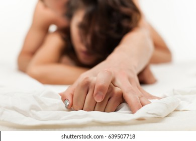 Sensual beautiful young couple is having sex on bed. Female hand pulling white sheets in ecstasy, orgasm. Love concept. Wellness. Couple in love. Orgasm concept. Beautiful lady and guy in erotic pose.