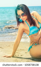 Sensual bikini woman on the sea beach with sunglasses. A woman in a swimsuit and sunglasses sitting on the beach at sea. Behind her, a blue sea and some rocks.