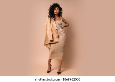 Sensual black woman with beautiful wavy hairs  in golden shiny dress posing over beige background. Full lenght.