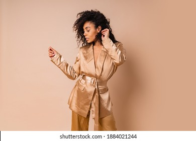 Sensual black woman with beautiful wavy hairs in elegant  golden satin suit posing over beige background. Spring fashion look.